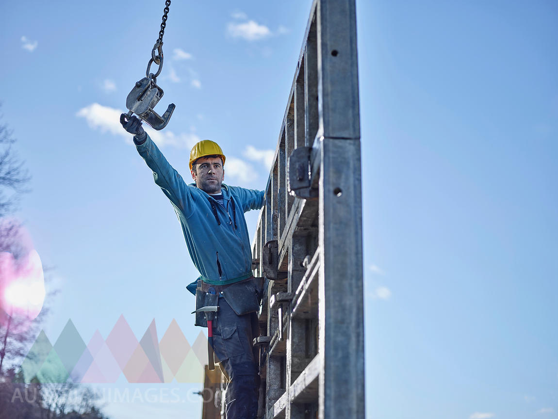 Construction worker reaching for hook of crane