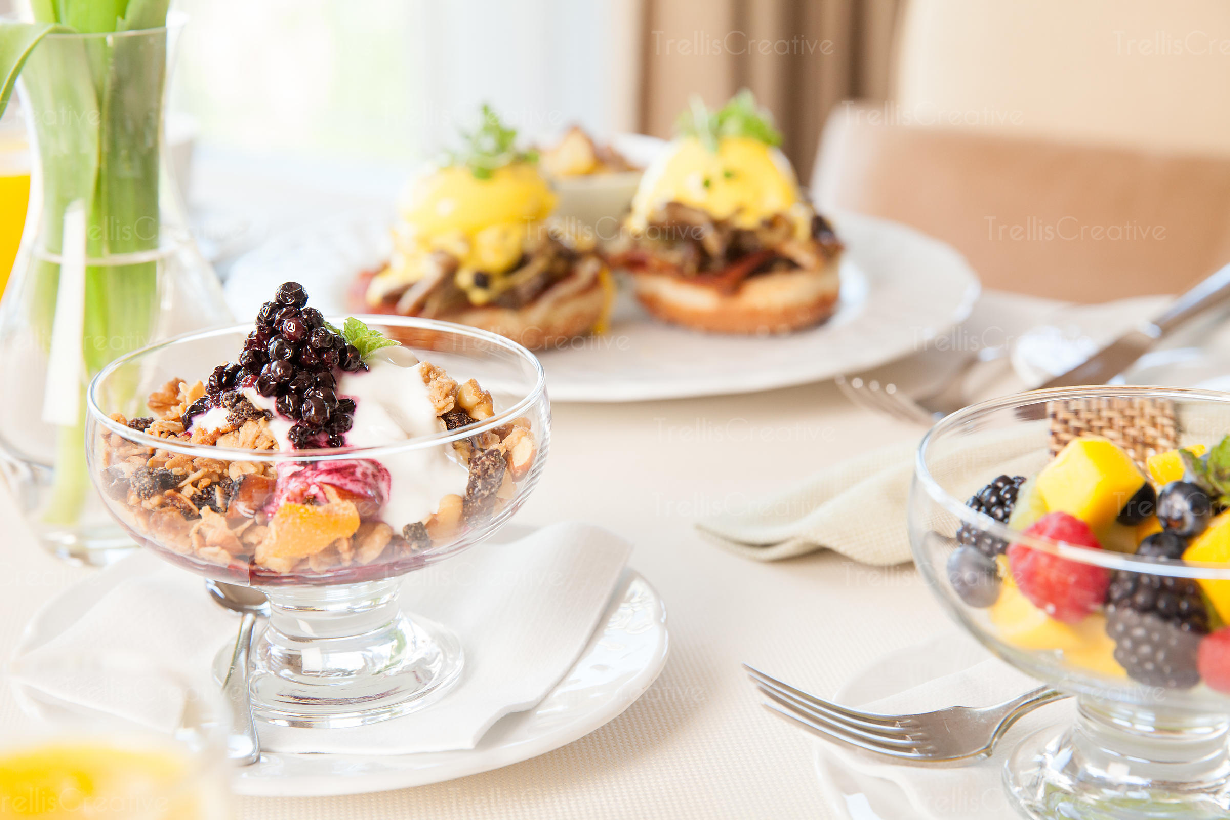 Gourment breakfast with fresh fruits, parfiets and eggs benedicts