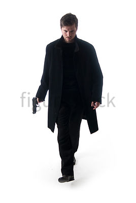 A Figurestock image of a man in a black coat, walking with a gun – shot from eye level.