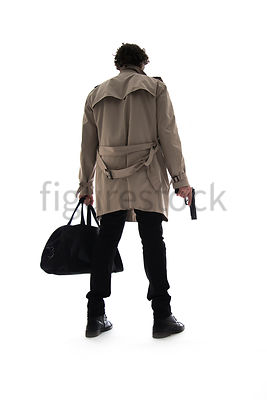 A Figurestock image of a man in a mac, standing, holding a black bag and a gun – shot from low level.