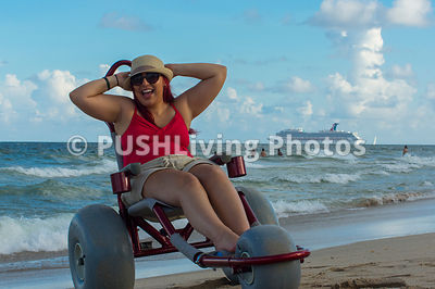 Young woman enjoying the ocean in a beach wheelchair