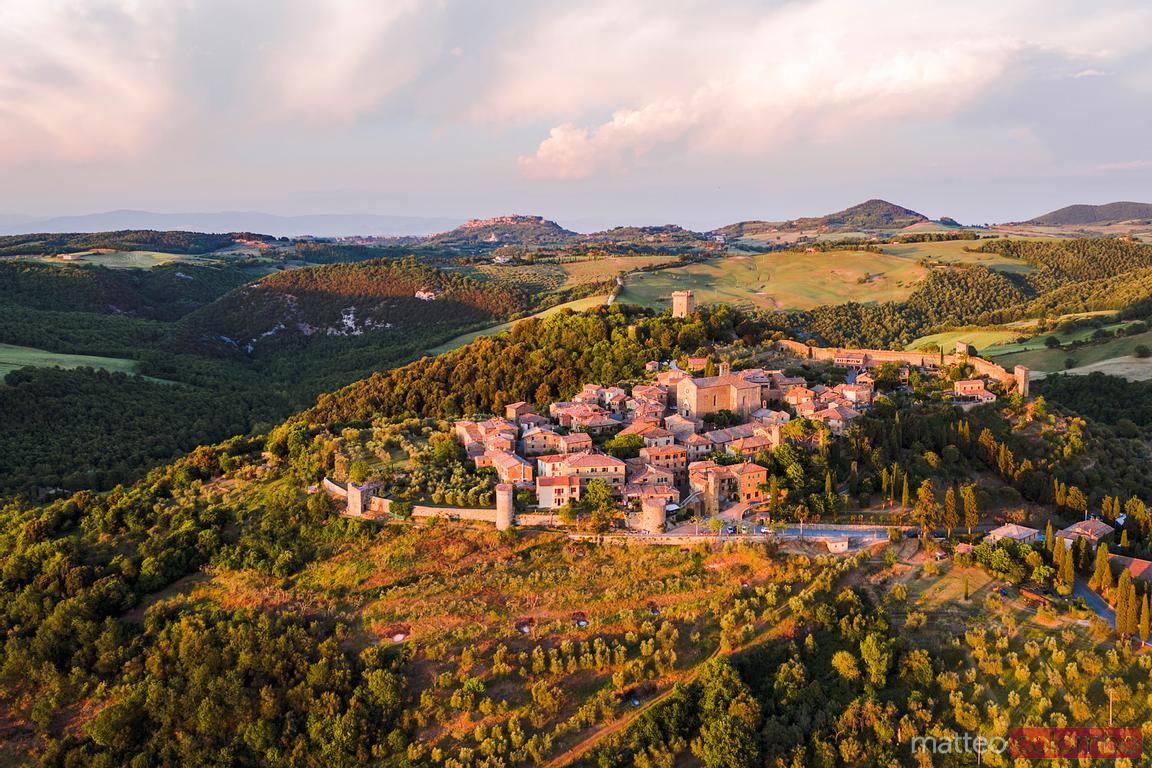 Aerial sunset over medieval town, Val d'Orcia, Tuscany, Italy
