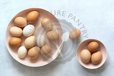 Brown and white hen eggs in two bowls.