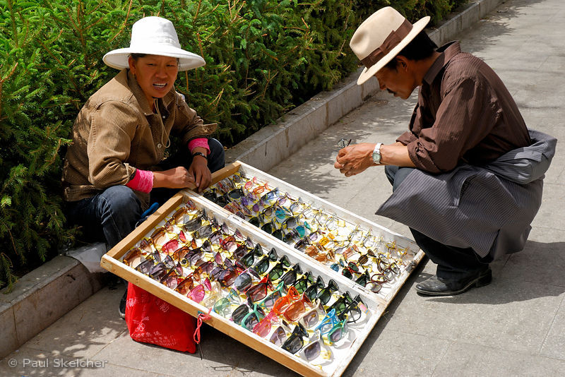 Street vendor sells sunglasses on the Tsekor, sacred pilgrim circuit that encircles the outer walls of the Potala Palace, Lha...