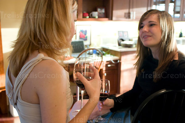 Two young women talk and drink red wine