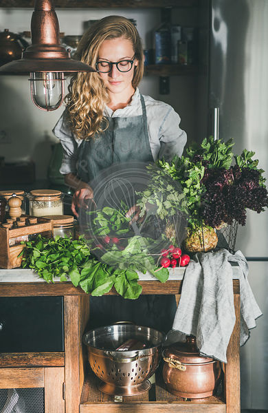 Young woman cutting herbs and vegetables in kitchen