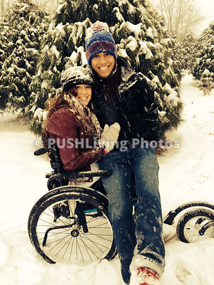 Young woman in a wheelchair enjoying a snowfall with her boyfriend.