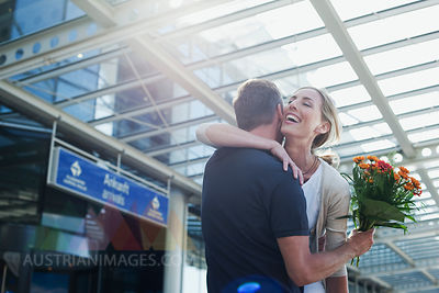 Germany, Leipzig-Halle, Airport, Couple embracing, Man holding flowers