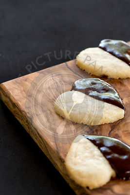 homemade chocolate dipped heart biscuits or cookies on olive wood board, against black background