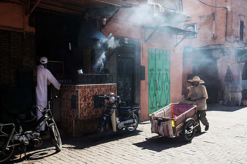 Man Wheeling Cart in Marrakech Street