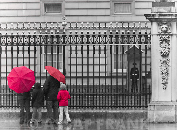 London, Family standing by fence outside Burmingham Palace
