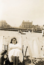 NOT FOR MISERY MEMOIR USAGE - An old family photograph of a woman sitting in a deck chair on a seaside beach.