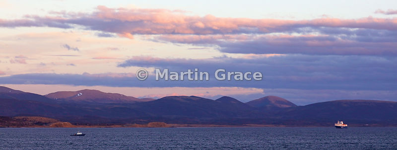 The Beagle Channel at dusk with a tourist vessel and a small boat, Tierra del Fuego, Argentina