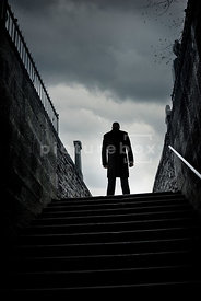 An atmospheric image of a mystery man standing at the top of some steps to a graveyard.