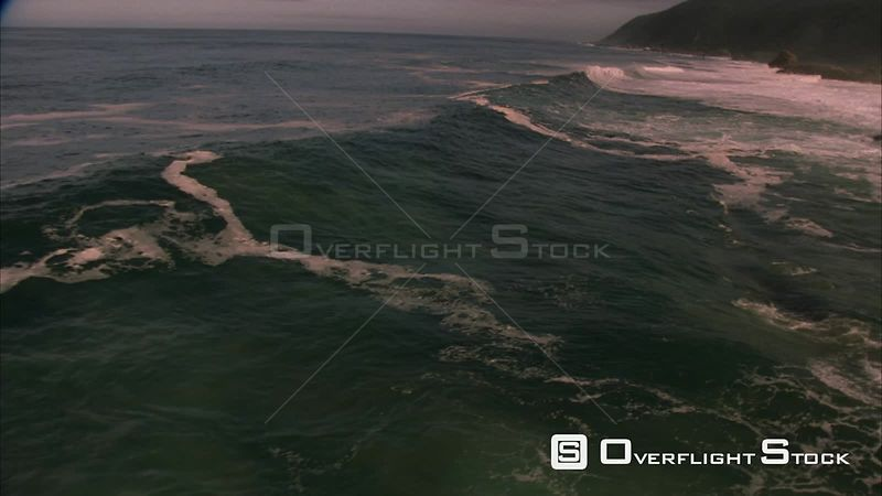 Slow motion aerial shot of waves crashing against the rocky coastline. Eastern Cape South Africa