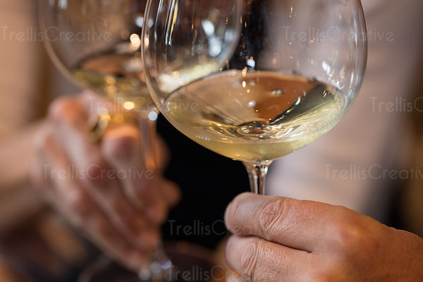 Close-up of two people holding wine in glasses