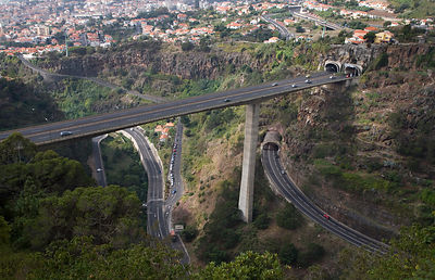 Aerial view of dual carriageway road carried by bridge high over a valley above other roads, near Funcal, Madeira, November