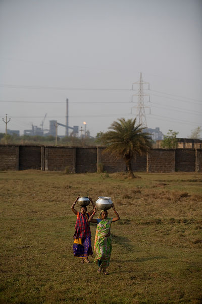 India - Orissa  - Tribal women gather water in the shadow of the Jindal Steel Plant