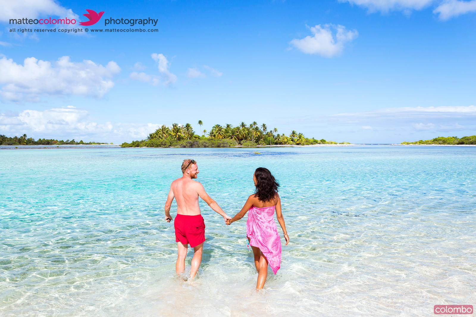 Happy couple of tourists in the lagoon of Tikehau, French Polynesia