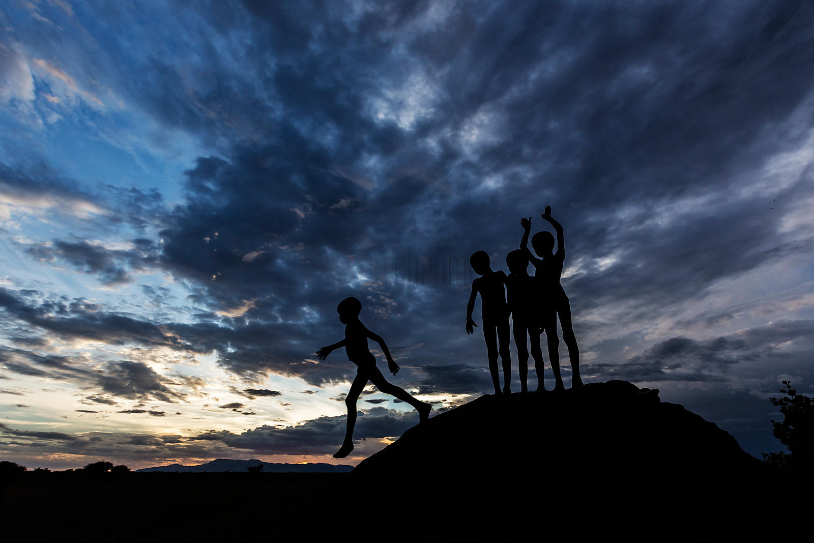 Silhouette of African Boys on an Anthill
