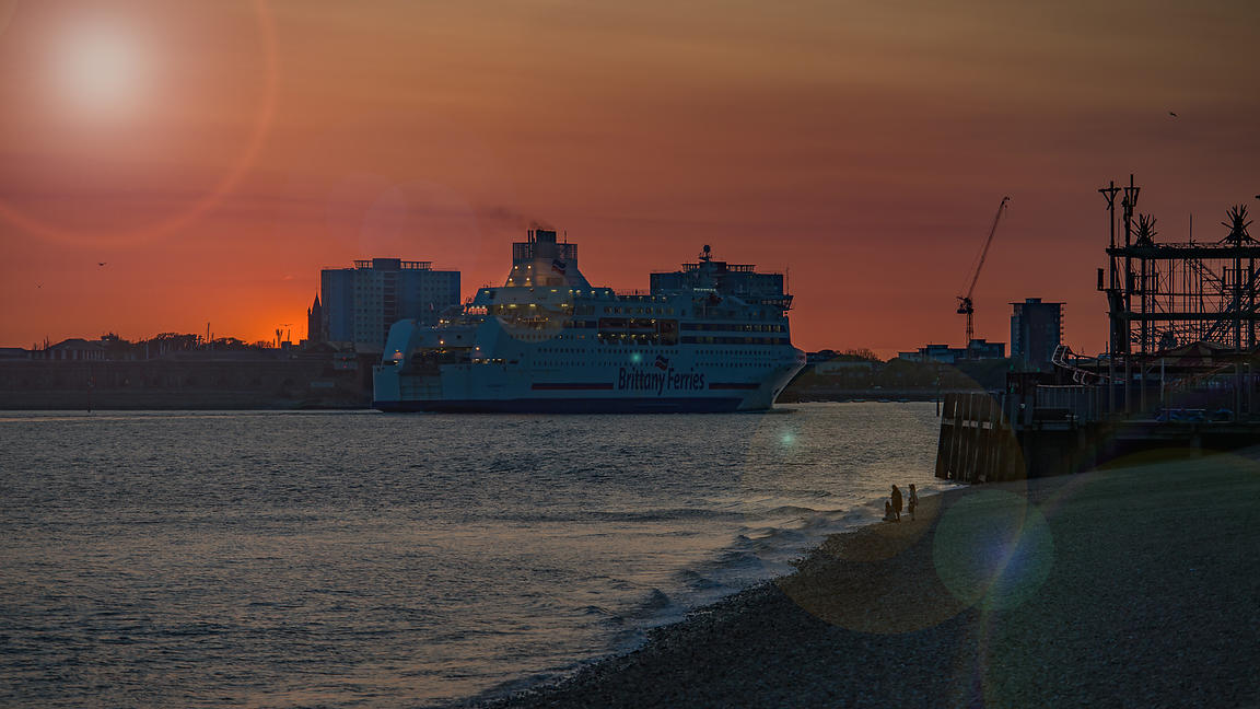 Brittany Ferry enters Portsmouth harbour at sunset with Sun Flare