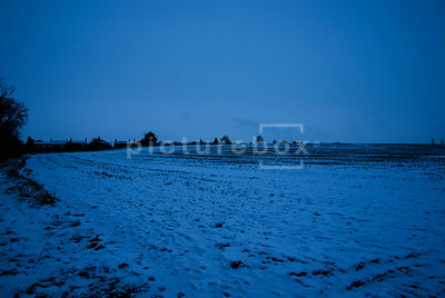An atmospheric image of a snow covered field, with some houses in the distance, on a winters morning.