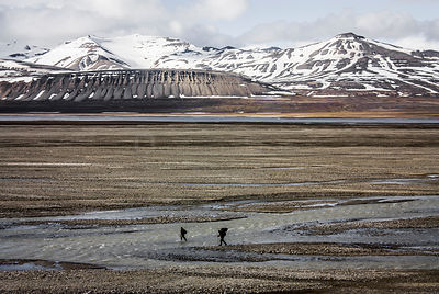Men crossing river in front of mountains, Svalbard, Norway, July.