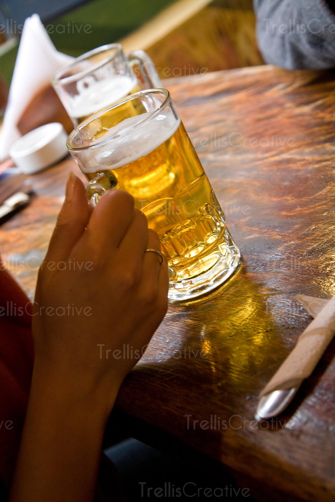 A young woman holds a mug of light beer