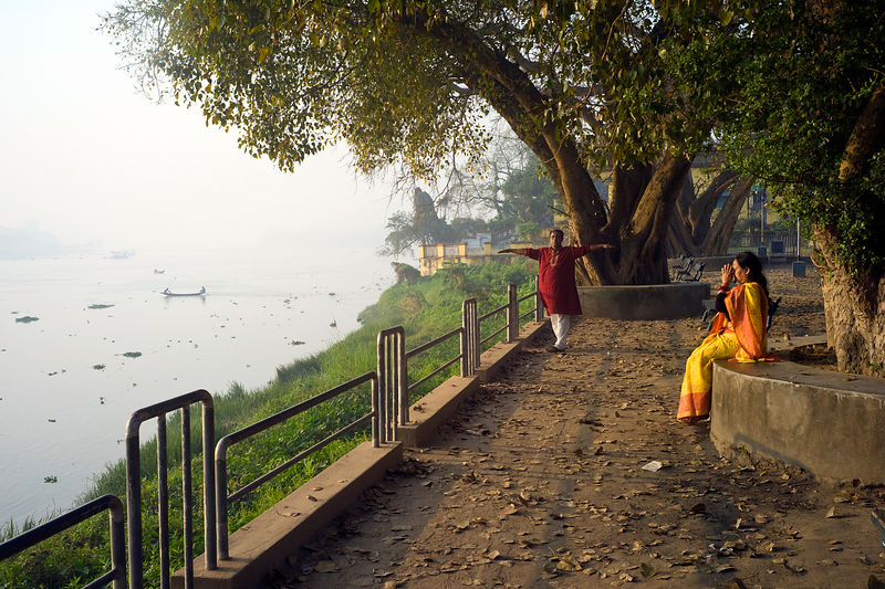 India - Chandannagar - A man and a woman do yogic exercises at dawn on the banks of Hooghley River