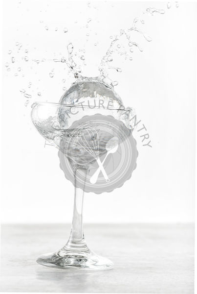 Large ice sphere splashing into coupe glass filled with gin