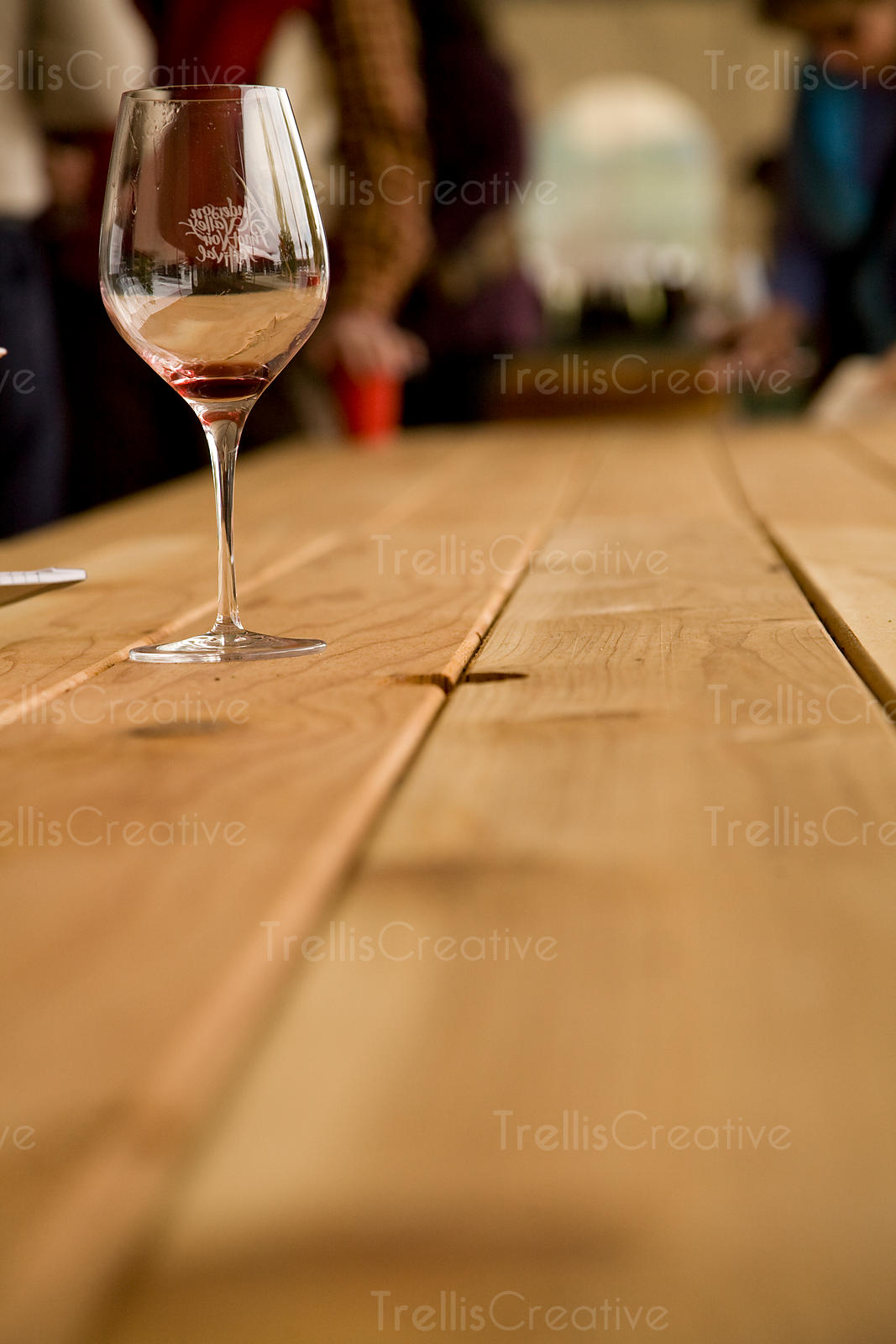An empty wine glass sits on a wooden picnic table