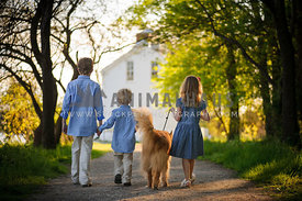 children walking with family dog down wooded path