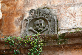 Detail of skull carving above entrance to old cemetery next to the Temple of the Holy Family / Templo de la Sagrada Familia, ...