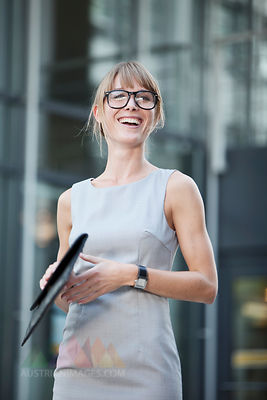 Germany, Bavaria, Munich, Young businesswoman wearing spectacles and holding purse, portrait, laughing