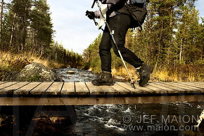 Hiker crossing a river on a wooden bridge