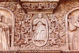 Detail of female figure (Virgin Mary?) surrounded by angels on main facade of cathedral, Puno, Peru