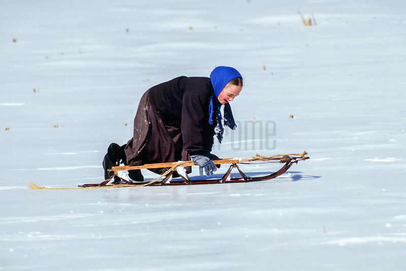 Amish Girl Playing on a Sled
