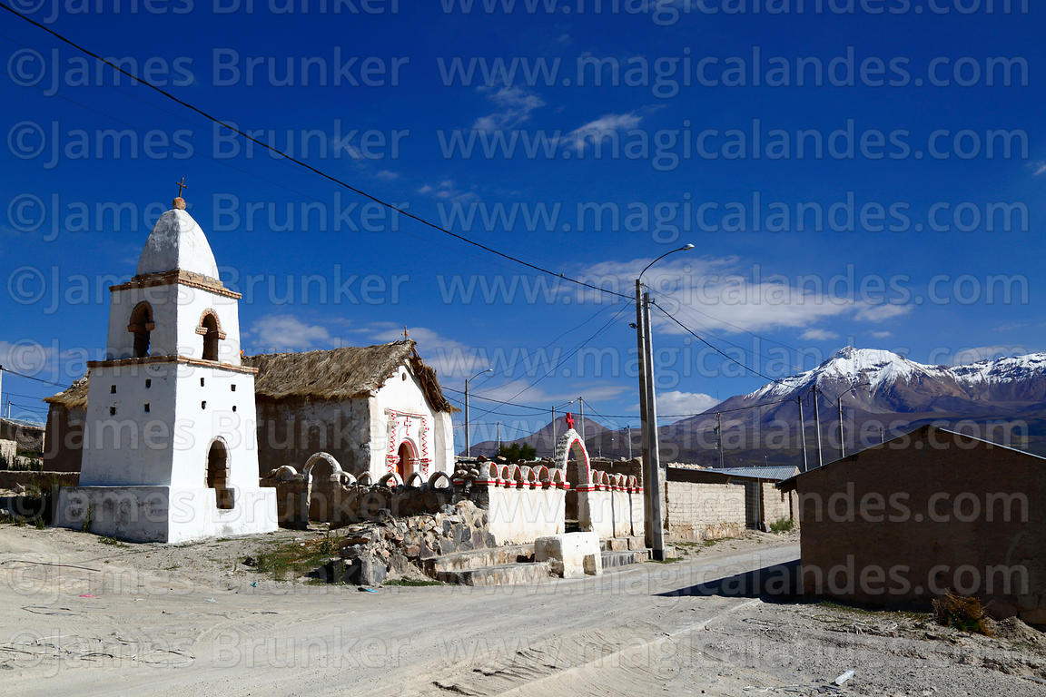 Rustic church and belfry in Cotasaya village, Cabaray / Cabaraya volcano in background, Region I, Chile