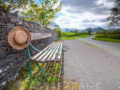 Bench with a hat on countryside road