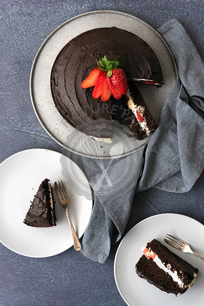 Round chocolate cake filled with cream and two slices of cake on plates.