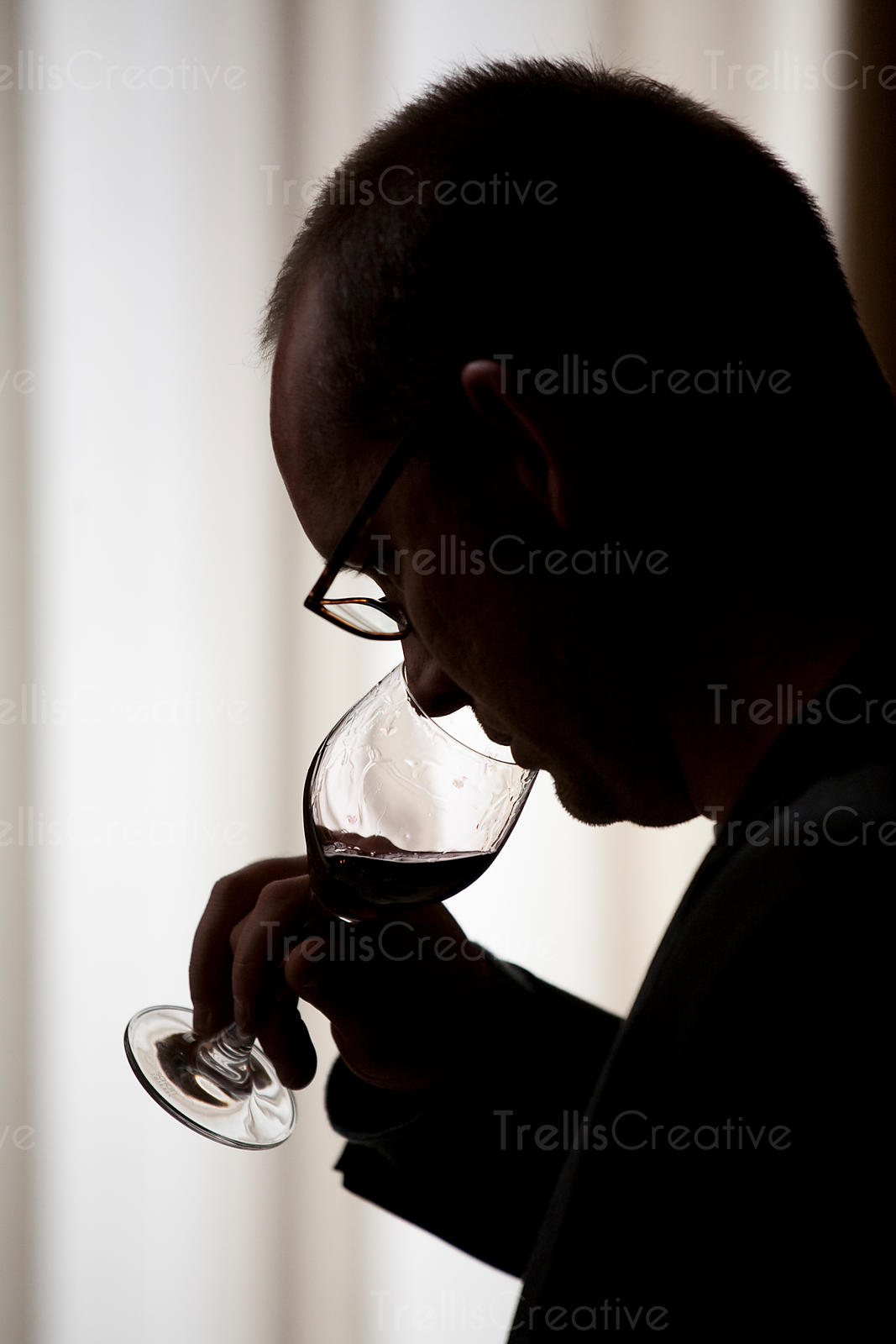 Silhouette of a man smelling a glass of red wine