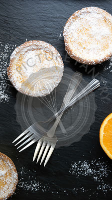 Two lemon tarts dusted with powdered sugar and two forks.