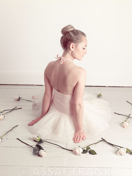 Young Ballerina sitting with roses on floor