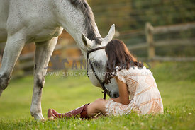 Girl kissing horse in pasture