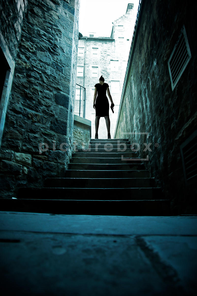 An atmospheric image of a mystery woman, holding a gun at the top of some dark steps.