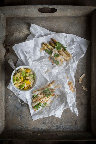 Asparagus satay and peanut dip served on sandwich paper and grey vintage tray. Top view