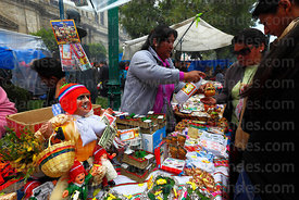 Ekeko on stall selling miniatures, seller is blessing client with alcohol, Alasitas festival, La Paz, Bolivia