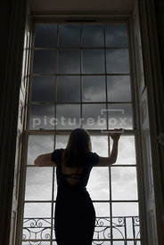 An atmospheric image of a mystery woman staring out at the gathering storm clouds through a Georgian window.