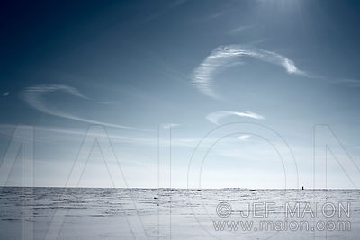 White clouds and blue sky over frozen sea