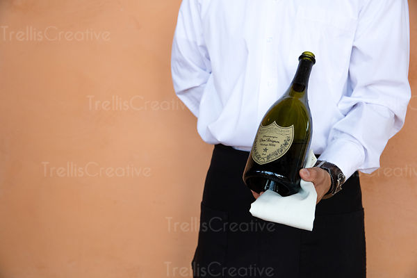 A waiter holding a sparkling wine bottle and napkin in hand